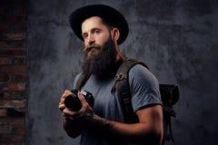 一个英俊的有胡子的旅客的画象一个帽子的有背包和被刺字的胳膊的,举行一台照片照相机,在a 库存照片