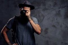 一个英俊的有胡子的旅客的画象一个帽子的有背包和被刺字的胳膊的,做与照片照相机的一张照片 图库摄影