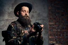 一个英俊的有胡子的旅客的画象一件帽子和伪装夹克的,有背包和被刺字的胳膊的,拿着一张照片 免版税库存图片