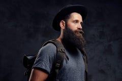 一个英俊的有胡子的旅客的画象帽子的有背包的 隔绝在黑暗的背景 免版税图库摄影
