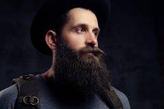 一个英俊的有胡子的旅客的画象帽子的有背包的 隔绝在黑暗的背景 库存照片