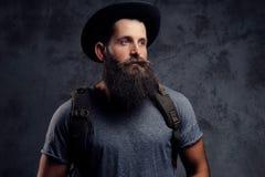 一个英俊的有胡子的旅客的画象帽子的有背包的 隔绝在黑暗的背景 免版税库存照片