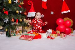 一个英俊的男孩对很多圣诞节礼物高兴 免版税库存图片