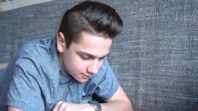 一个英俊的男孩少年在一个灰色沙发,棕色眼睛读一本书 库存图片