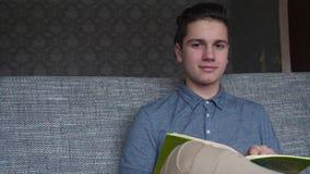 一个英俊的男孩少年在一个灰色沙发,棕色眼睛读一本书 库存照片