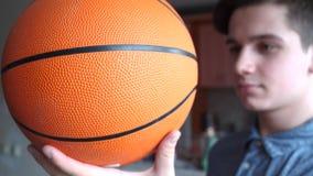 一个英俊的男孩少年拿着一basketballl 库存图片