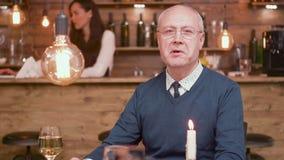 一个英俊的老人的画象谈话与在酒吧的照相机 股票视频