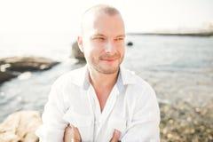 一个英俊的年轻人的画象在阳光下由海 库存图片