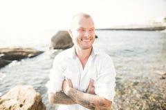 一个英俊的年轻人的画象在阳光下由海 免版税图库摄影