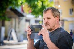 一个英俊的年轻人的画象有手机的在手上 免版税库存照片