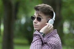一个英俊的年轻人的画象有耳机的在公园 免版税库存照片