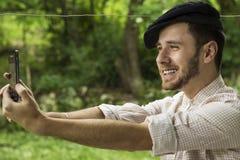 一个英俊的年轻人的画象有采取selfie电话的盖帽的 免版税库存图片