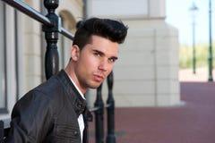 一个英俊的年轻人的画象黑皮夹克的 库存照片