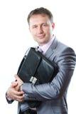 一个英俊的年轻商人的画象与袋子的在白色隔绝的衣服 免版税库存照片