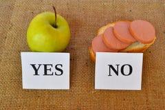 一个苹果和一个三明治与香肠-有用和有害的快餐 免版税库存图片