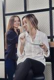 一个茶会的两个女孩在咖啡馆,其中之一的柜台拿着在嘴的一把匙子 免版税库存图片