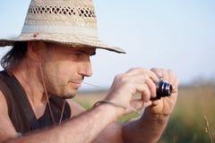 一个草帽的人与照相机 免版税库存图片