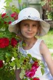 一个草帽的在庭院玫瑰丛附近,夏令时假期一个小女孩 库存照片