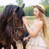 一个草帽的女孩有马的 免版税图库摄影