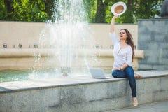 一个草帽的美丽的企业女孩浅黑肤色的男人,有在一个喷泉的一台膝上型计算机的在街道和摇她的手 免版税库存照片