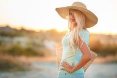 一个草帽的美丽的妇女在日落 图库摄影