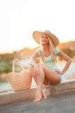 一个草帽的美丽的妇女在日落 免版税库存照片