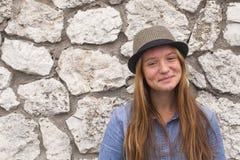 一个草帽的迷人的女孩在一个石墙的背景 免版税库存图片