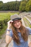 一个草帽的年轻可爱的女孩在公园 自然 免版税库存图片