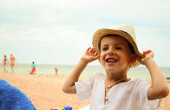 一个草帽的滑稽的男孩在海滩 免版税库存照片