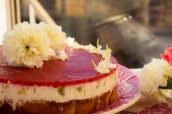 一个草莓蛋糕的特写镜头从边的在与果冻和果子的白色batskground松糕在栏杆的背景 12月 免版税库存照片