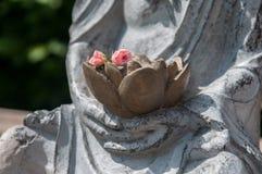 一个菩萨雕象的细节与花的在手上 免版税库存图片