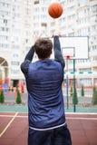 一个蓝球运动员在一个开放体育场内,投掷球入圆环,提起他的手 免版税库存图片