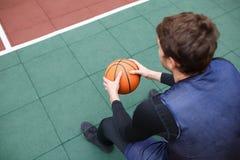 一个蓝球运动员在有一个球的一个开放体育场在他的手上坐休息 免版税图库摄影