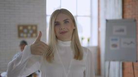 一个蓝眼睛的白肤金发的女孩的画象 友好的办公室工作者显示赞许 配合概念4K 股票录像