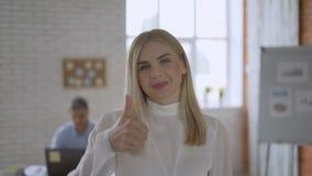 一个蓝眼睛的白肤金发的女孩的画象 友好的办公室工作者显示赞许 配合概念4K 影视素材