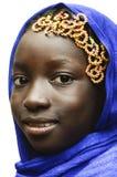 一个蓝色典型的非洲人遮掩的华美的微笑的非洲女小学生Hijab 免版税库存图片