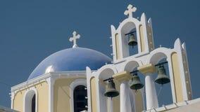 一个蓝色圆顶和四教堂钟的低角度射击在fira,santorini 免版税库存图片