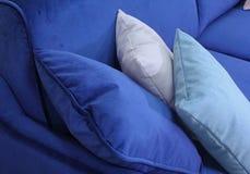 一个蓝色天鹅绒沙发的片段有三个枕头的 免版税库存照片