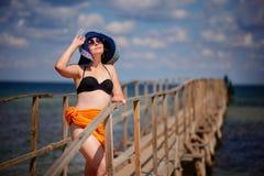 一个蓝色帽子的女孩沿码头去 免版税库存照片