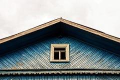 一个蓝色房子的门面有一个小窗口的在天空背景 免版税库存照片