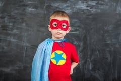 一个蓝色披肩红色面具的男孩超级英雄和有星的一件红色T恤杉 图库摄影