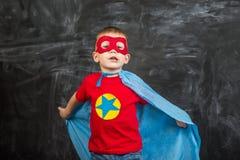 一个蓝色披肩红色面具的男孩超级英雄和有星的一件红色T恤杉 免版税库存照片