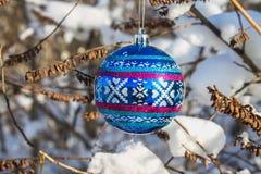 一个蓝色新年球在与雪的一个分支垂悬 空白背景圣诞节玻璃查出的范围的玩具 图库摄影