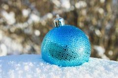 一个蓝色新年球在雪在 空白背景圣诞节玻璃查出的范围的玩具 库存照片