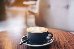 一个蓝色杯子的特写镜头图象与拿铁艺术的热的拿铁咖啡在葡萄酒木桌上 免版税库存照片