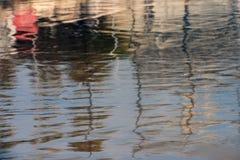 一个蓝色水坑,红色和交通事故多发地段的表面上的抽象反射在左上部角落的,在水挥动 库存图片
