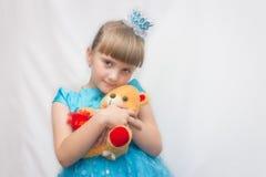 一个蓝色礼服和冠的年轻公主,在白色背景和拿着一个玩具熊 子项的纵向 免版税库存图片