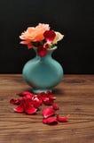一个蓝色花瓶与上升了一个丢失了它的瓣的地方 免版税图库摄影