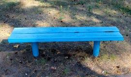 一个蓝色长木凳在公园 库存照片