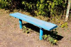 一个蓝色长木凳在公园 免版税库存照片